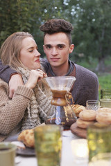 An apple orchard in Utah. A couple embracing, food and drink on a table.