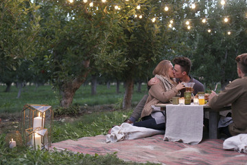 An apple orchard in Utah. Couple sitting on the ground, kissing, food and drink on a table.