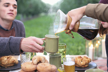 An apple orchard in Utah. Group of people sitting round a table with food and drink, pouring coffee.