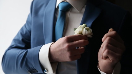 The groom wears a tie and cufflinks boutonniere