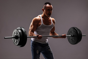 Strong muscular man lifting a heavy barbell