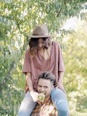 An apple orchard in Utah. man carrying a woman on his shoulders, eating an apple.