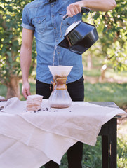 An apple orchard in Utah. man standing at a table, making coffee.