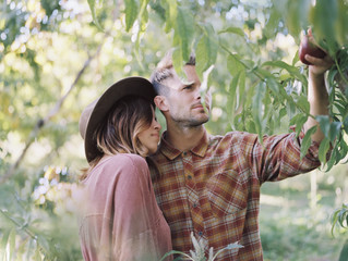 An apple orchard in Utah. A couple standing by an apple tree, holding an apple.