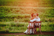 Beautiful young bride and groom kissing sitting on chairs