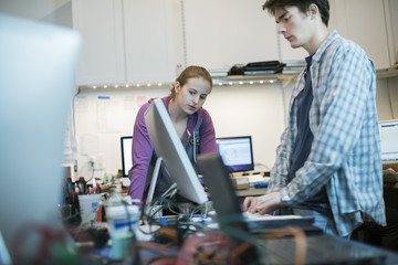Two people, a man and woman standing at the counter in a computer repair shop.