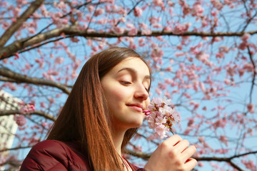 Happy woman with flowers of cherry blossom tree