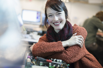 Computer Repair Shop. A woman smiling and leaning on a workshopcounter.