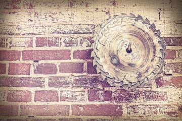 Retro style circular saw blade on brick wall.