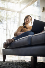 Low angle view of a woman sitting on a sofa looking at her laptop.