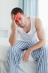 Portrait of a depressed man sitting on his bed