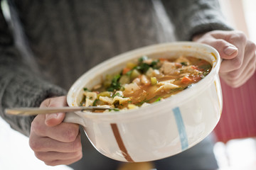 Close up view of a man holding a bowl with a vegetable stew.