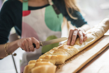Close up of a woman wearing an apron, sitting at a table, slicing a baguette.