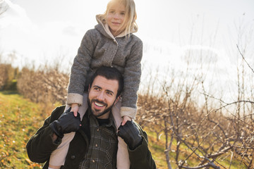 A man giving a child a ride on his shoulders.