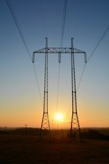High voltage power lines with big and tall pylons.