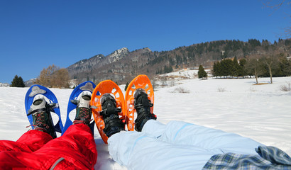 couple with blue and orange snowshoes in the mountains