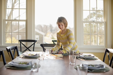 A young girl setting the table with plates and cutlery.