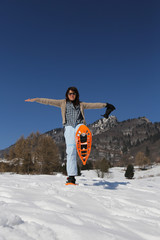 Beautiful smiling woman with snowshoes in winter