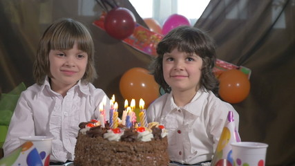 Young beautiful sisters blowing candles on a birthday cake