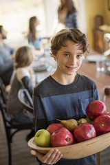 A boy carring a wooden tray of apples.
