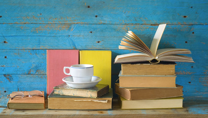 books, one opened with spectacles and a cup of coffee
