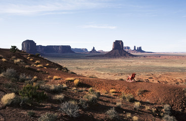 The landscape and eroded sandstone buttes and structureof Monument Valley. A single wooden chair.