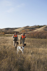 Two men, bird hunters, with shotguns, carrying the day's bagmof dead birds, and a spaniel dog.