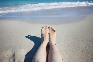 legs on the beach, female feet in  sand