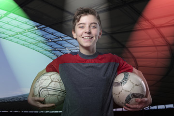proud, smiling teenage boy holding two soccer ball's, with color