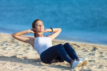 Sit. Fitness woman doing sit ups exercising on beach. Sporty