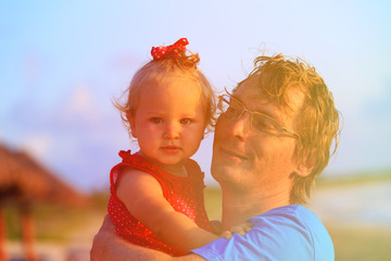 father and cute little daughter on summer beach