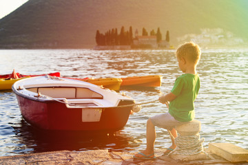 little boy fastening boat at sunset on the sea