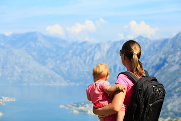 mother with little daughter looking at mountains