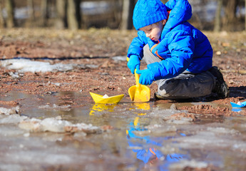 little boy plaing with paper boats in spring puddle
