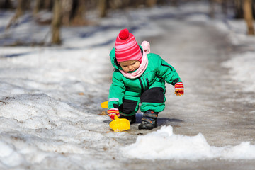 little girl digging snow in winter