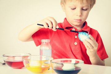 little boy painting eggs for easter
