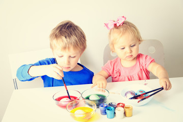little boy and toddler girl painting eggs for easter