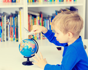 little boy playing with toy airplane flying around the globe