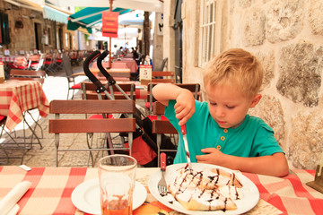 little boy eating in city cafe on summer day