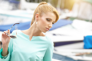 Beautiful woman near the boats and yachts. Outdoors, lifestyle