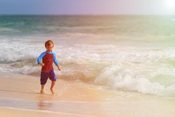 happy little boy running on sand beach