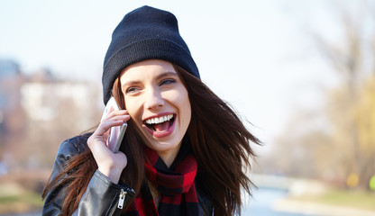 Young beautiful smiling woman talking on cell phone