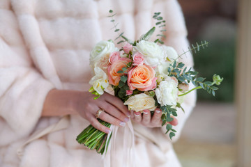 Beautiful wedding bouquet of roses in hands of bride.