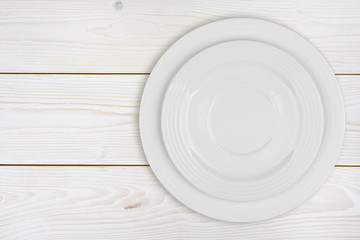 Pile of two white plates on bleached wooden plank background