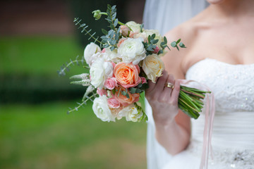 Beautiful wedding bouquet of roses in hands of bride.