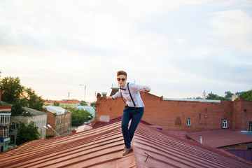 Happy hipster on the edge of the roof