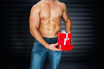 Composite image of attractive bodybuilder with gifts