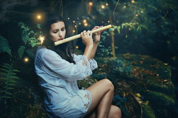 Beautiful forest nymph playing  flute with fairies