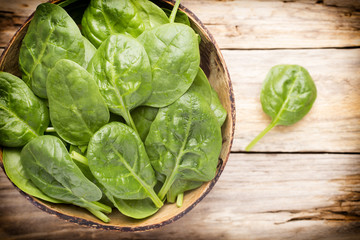 Spinach on the bowl, wooden background.