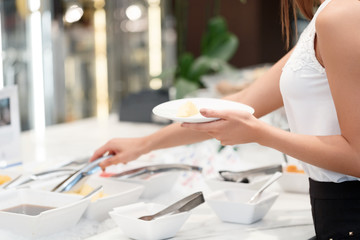 Businesswoman chooses a meal at business buffet